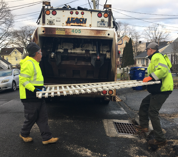 City employees picking up discarded picket fence to throw into garbage truck