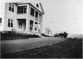 Black and white photo of an automobile in front of a house